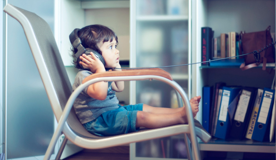 a toddler sits in a chair listening to music through headphones.