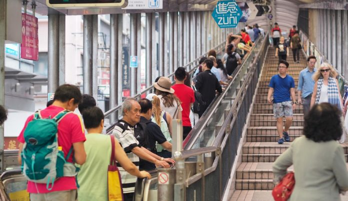 People in Hong Kong riding an escalator on the left and walking down stairs on the right.