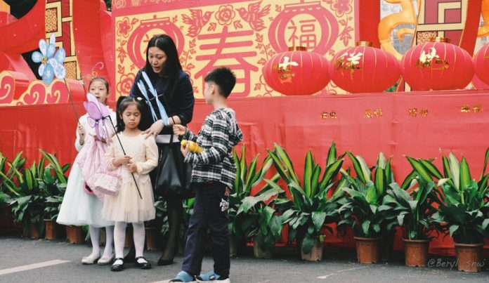 A Hong Kong mother stands with her boy and two girls who are holding whirligigs.