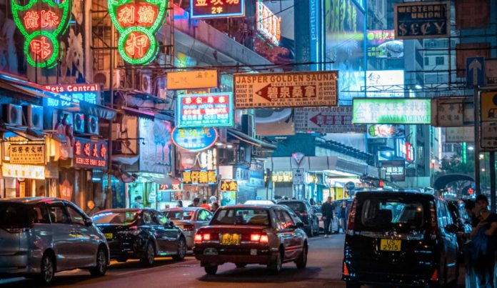Hong Kong street at night, with traffic and lit shop signs.
