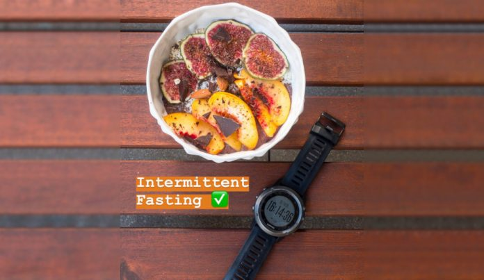 A bowl of fruit sits next to a watch on a wooden surface beside a label that says