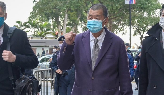 Jimmy Lai walking with fist raised.