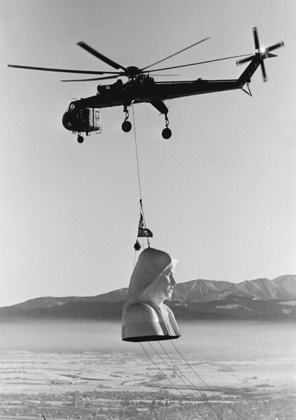 black and white photo from 1985 of helicopter carrying large virgin mary head in the air