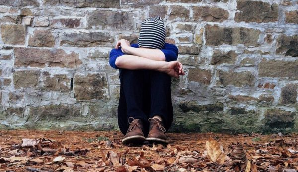 A person sits in front of a wall with knees drawn up to their chest and their head hanging down.
