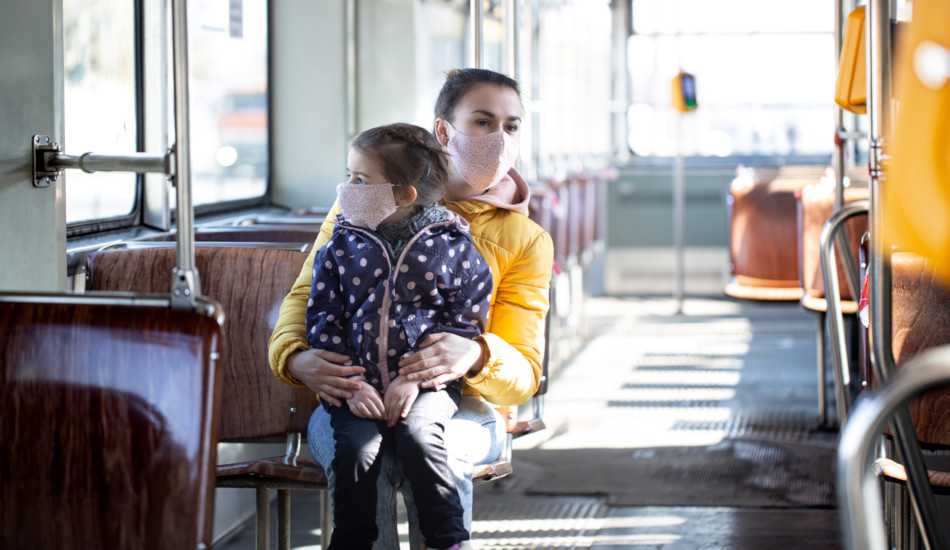A mother with her daughter on her lap, both wearing face masks, ride on public transportation.