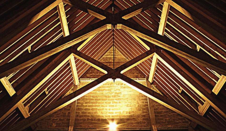 Roof beams inside a brick building.