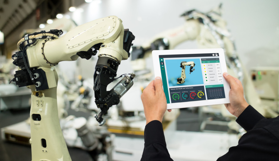 A factory worker uses a tablet to control a robotic army.