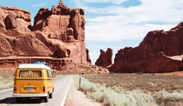 A yellow van travels through Arches National Park in Utah.