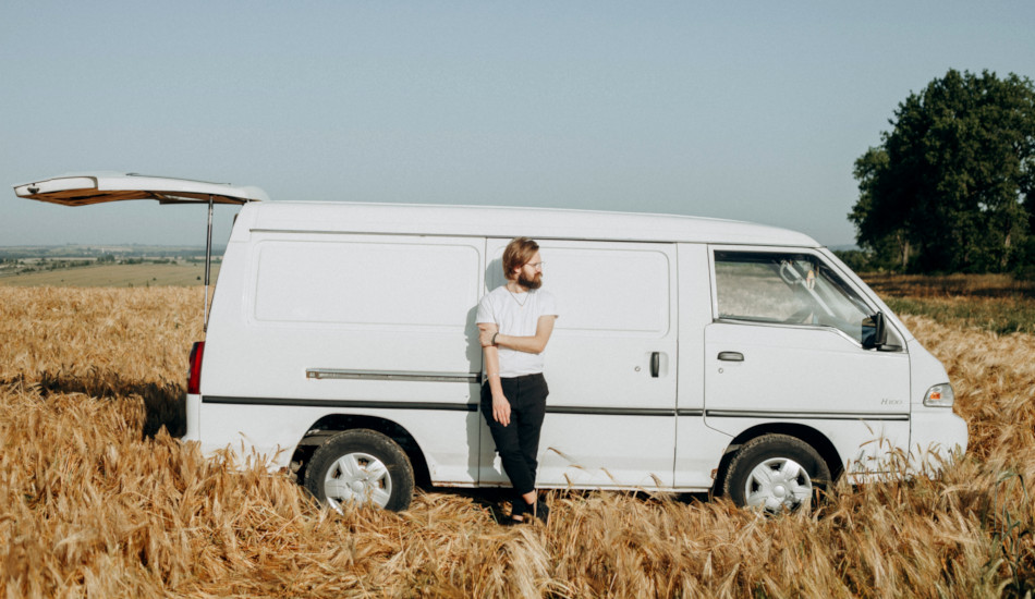 A man leaning against a white van parked in a wheat field.