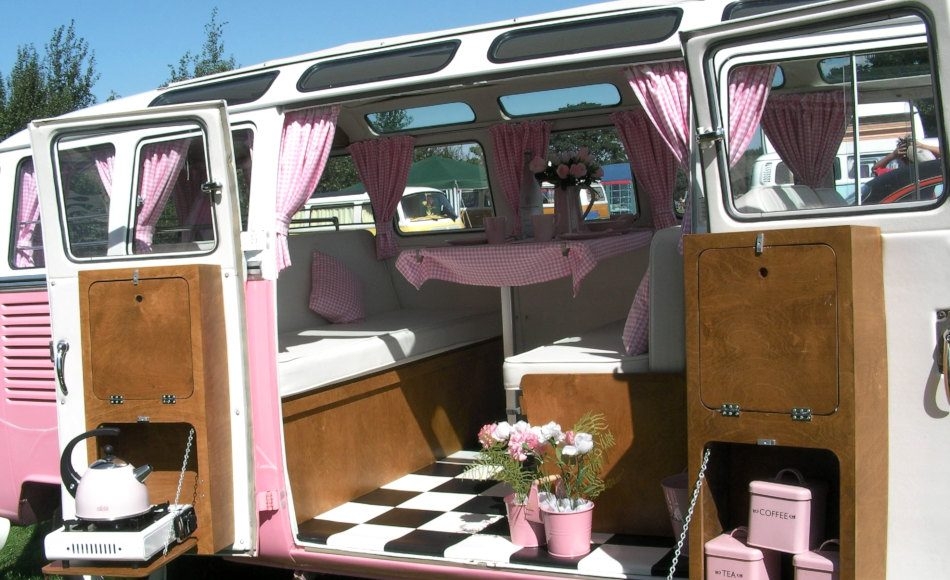 A pink and white campervan with pink and white curtains.