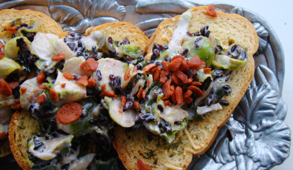 Crostini with brussels sprouts served on a silver platter.