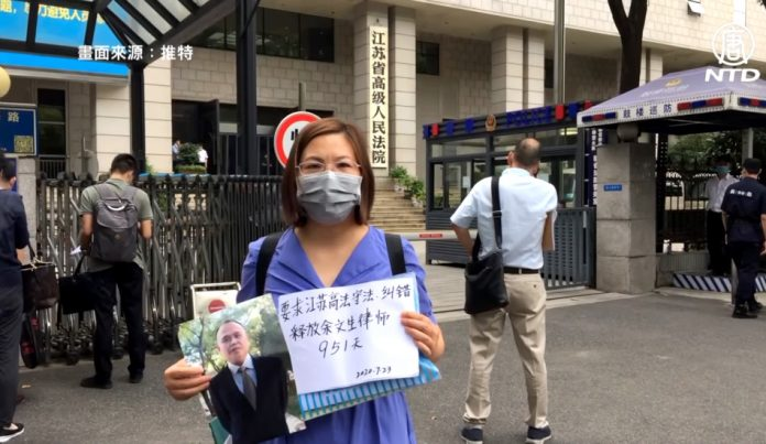 Xu Yan, the wife of lawyer Yu Wensheng, stands in front of the Jiangsu High Court holding a picture of her husband and a sign describing his mistreatment.