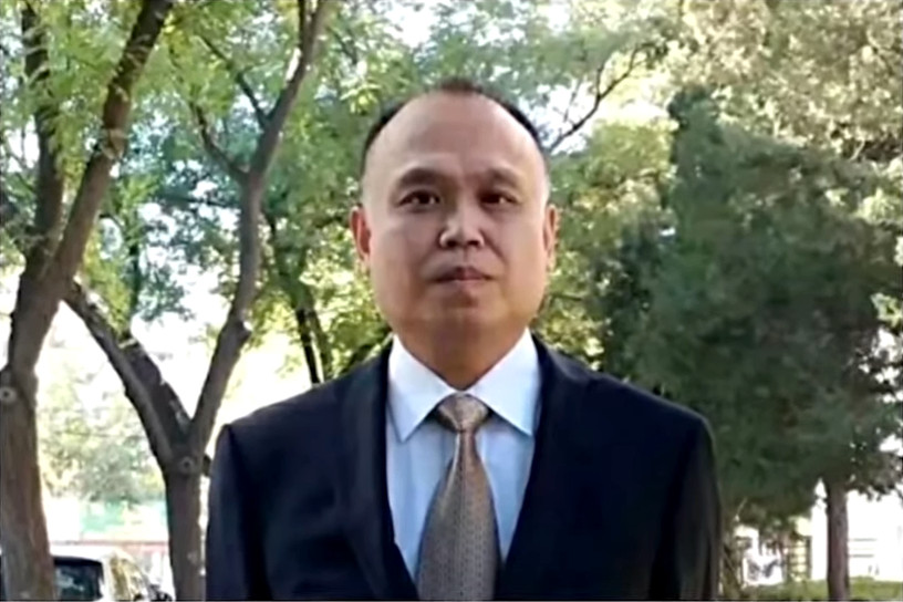 Chinese human rights lawyer, Yu Wensheng, wearing a suit and tie and standing in front of some trees.