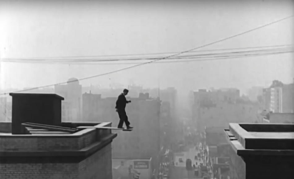 Buster Keaton walking on a plank on a high rise building with city in background