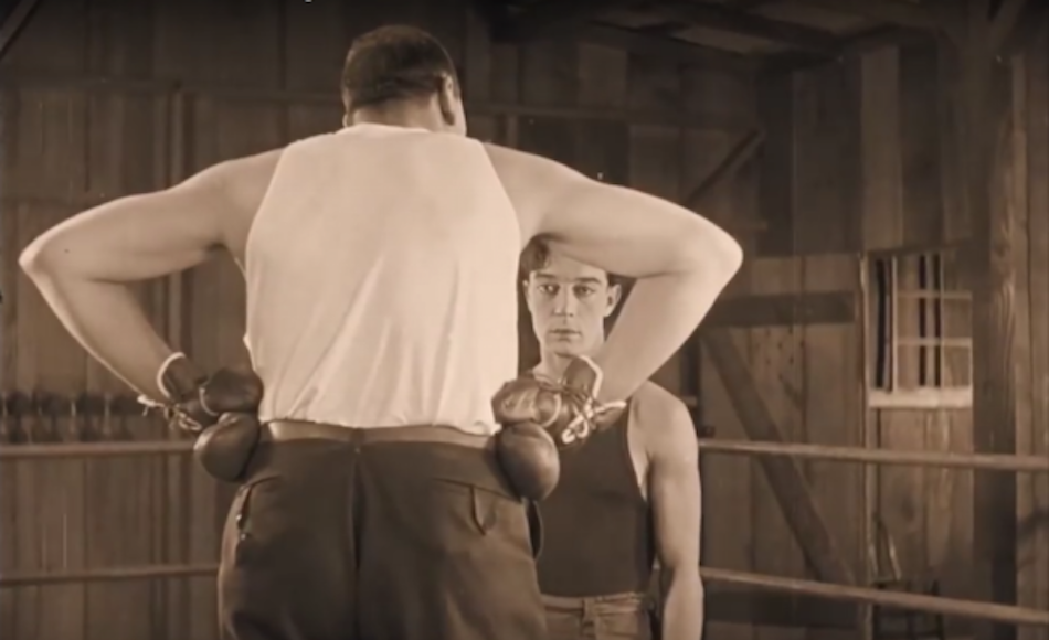 Buster Keaton's face framed by the triangle shape of a huge boxer with his back turned to camera and hands on his hips to create the triangle.