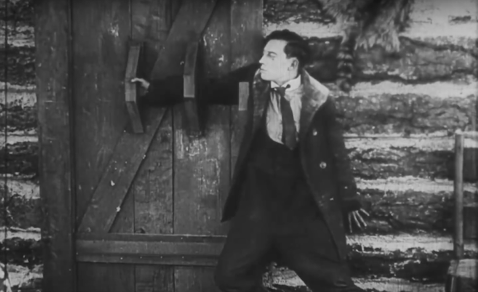 Buster Keaton with hand through door handles to secure a door (normally a big piece of wood would be in it's place)