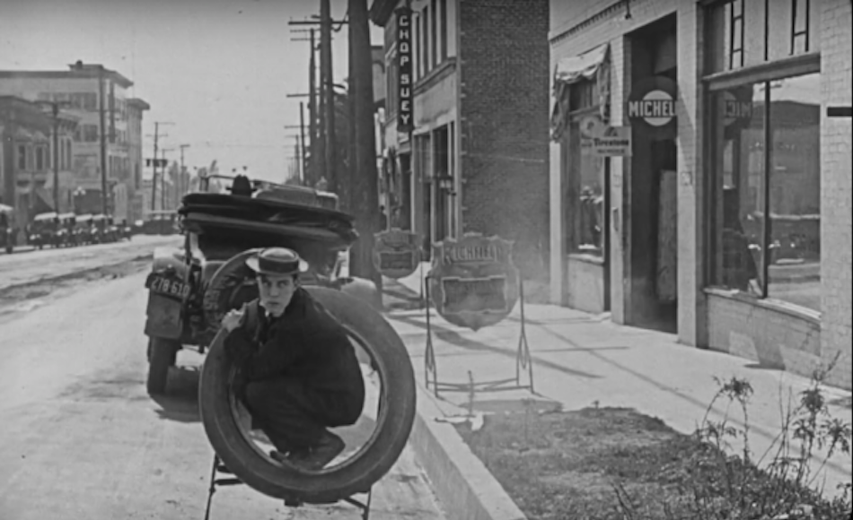 Buster Keaton crouches into a tyre that looks like it is secured to the back of an old car, the car drives away and leaves him crouching alone in a tyre looking comedic.