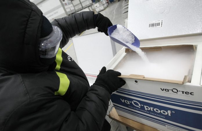 An employee of German company Va-Q-Tec fills dry ice into a vacuum-insulated cooling container at the company's headquarters in Wurzburg, south-central Germany, on December 1, 2020. Japan is facing a shortage of dry ice required to store Pfizer BioNTech's COVID-19 vaccine, which requires storage between -60 and -80 celsius.