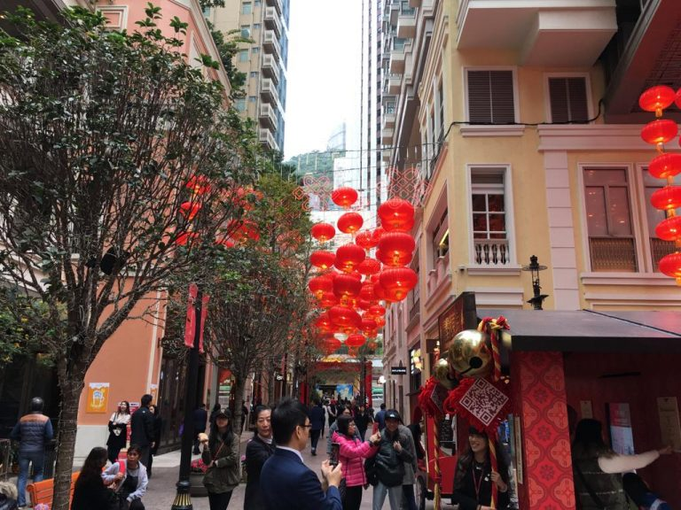 people walking over the beautifully decorated street in hong kong on chinese new year