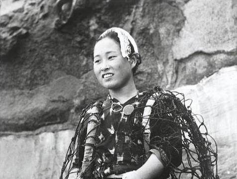 black and white photo of Ama diver holding a barrel and traditional tool and wearing a Tenugi (bandana) in her hair