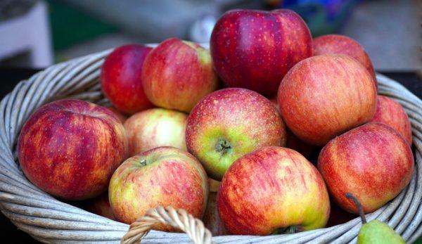 A wicker basket full of ripe red apples.