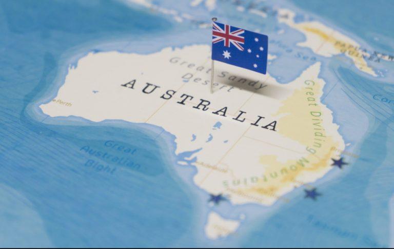 World map with a tiny Australian flag stuck into Australia.