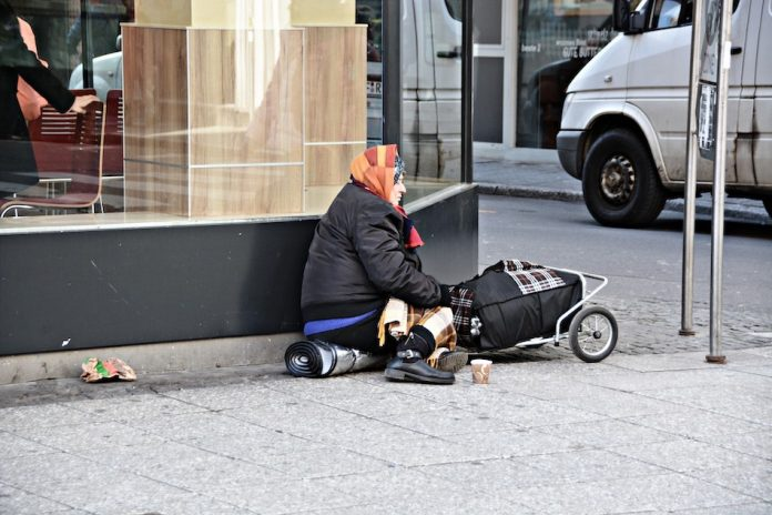 homeless lady sitting with trolley and warm jacket on pavement
