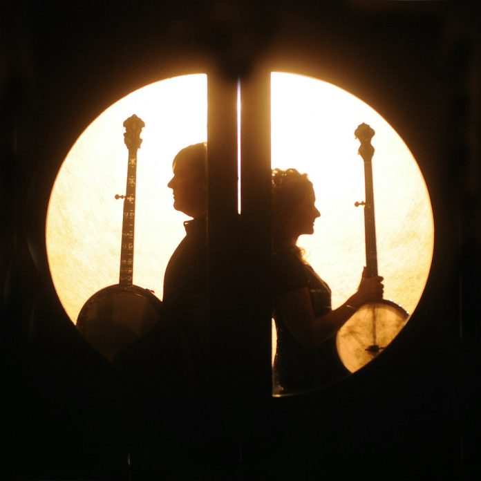 Béla Fleck & Abigail Washburn sit back to back holding their banjos as they are in shillouette with the light shining through a circular window