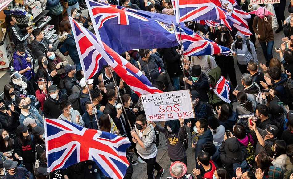 Protesters in Hong Kong carrying British flags and signs asking the UK to help British Nationals overseas.