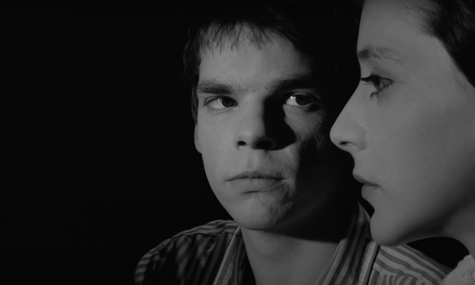 black and white film still from the film 'boy meets girl' boy gazes at girl as she looks ahead