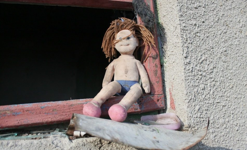 Doll looking a bit unkept in an abandoned house.