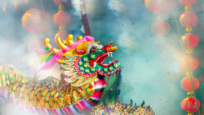 Chinese dragon with lanterns and smoke from firecrackers in the background