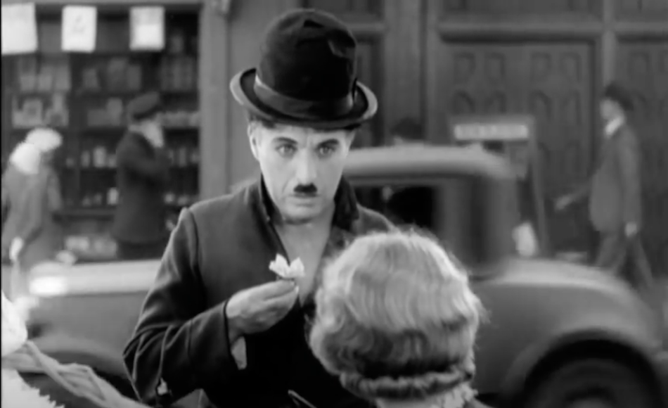 Charlie Chaplin holds a white flower about to hand to a lady