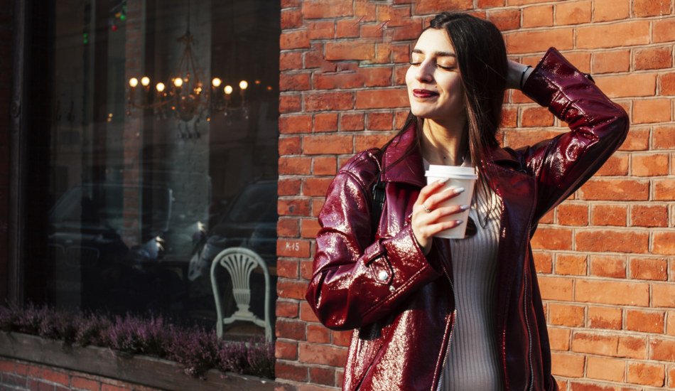 A smiling young woman in a maroon coat holds a beverage in a carry out cup while standing in front of a brick building.