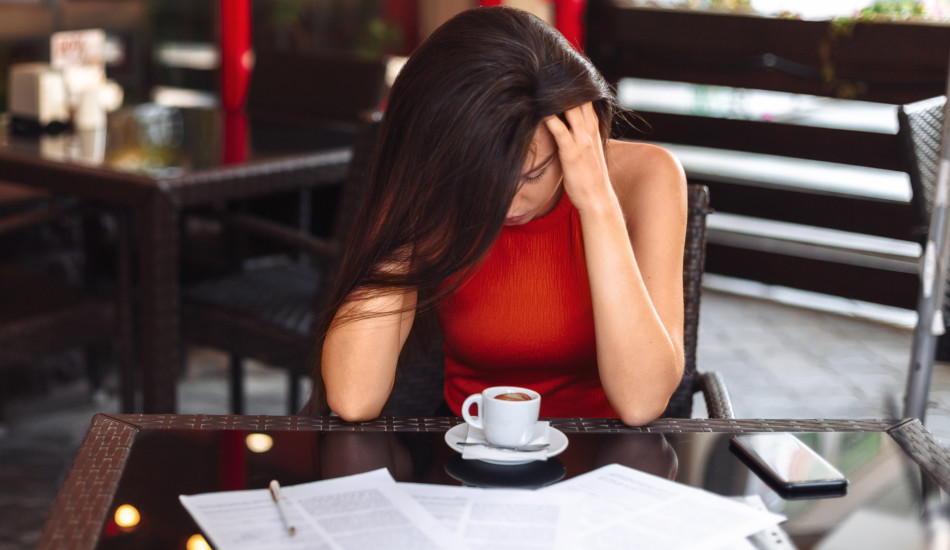 A young woman sitting at a table with a cup of coffee, some paperwork, and a cell phone while massaging her temples.