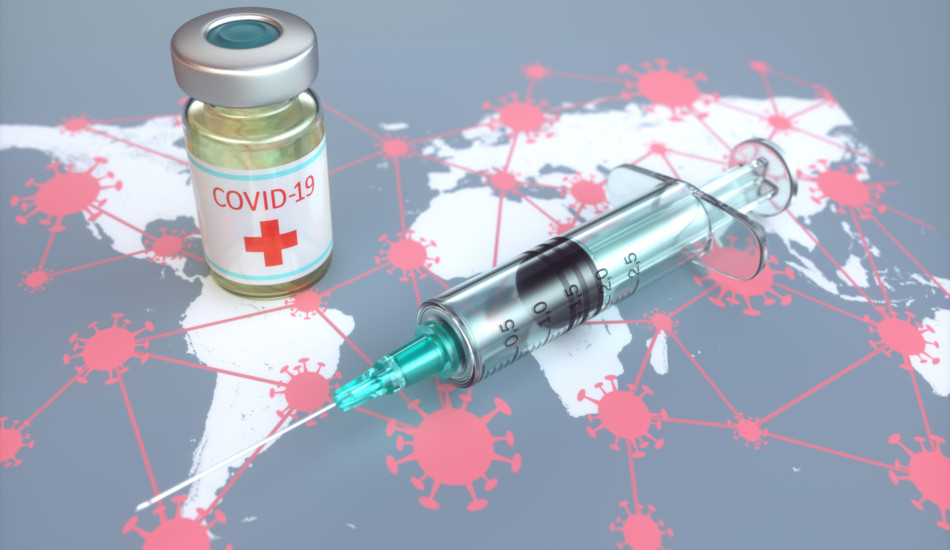 A vial and syringe sit atop a world map with the coronavirus drawn on it.