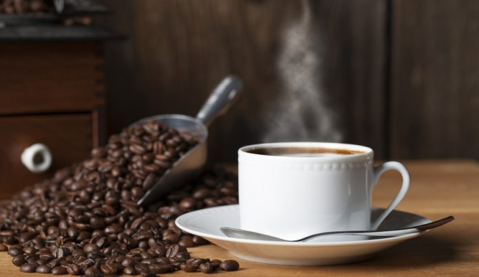 A steaming hot cup of coffee sits on a wooden table next to a metal scooper filled with coffee beans and an old fashioned coffee grinder.