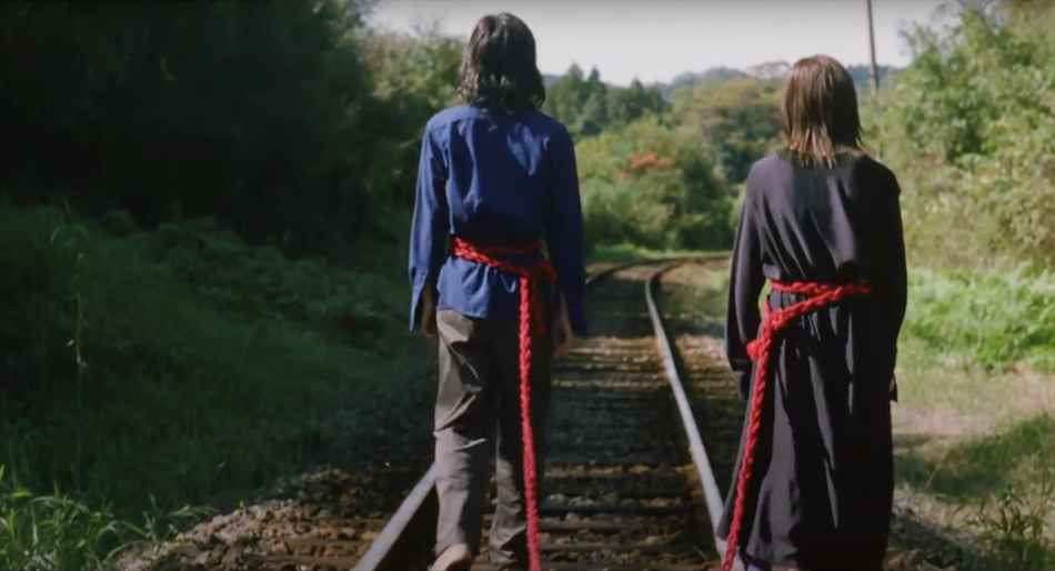 japanese couple walk along a railway track a red rope tied around each persons waist joining them together