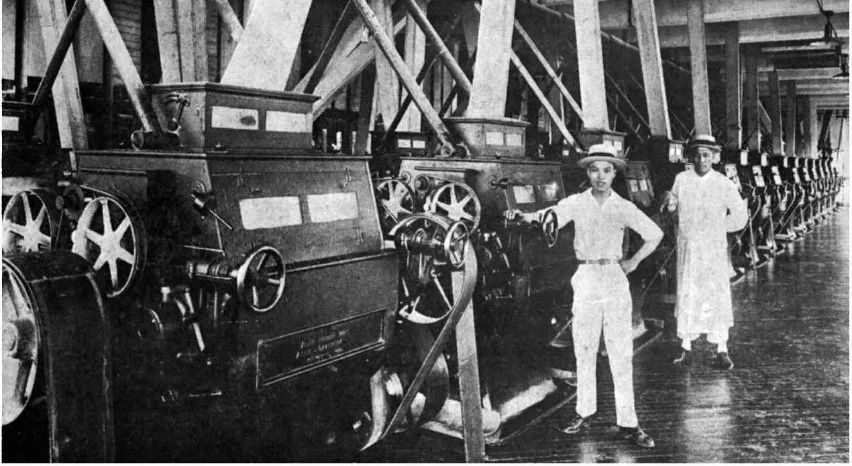 Machinery in the Rong Enterprises flour mill with two workers standing by.