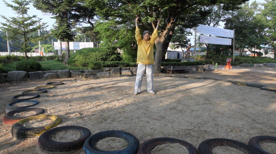 Yonghee practices the Falun Gong exercises there is a tree behind her and she wears a yellow jacket
