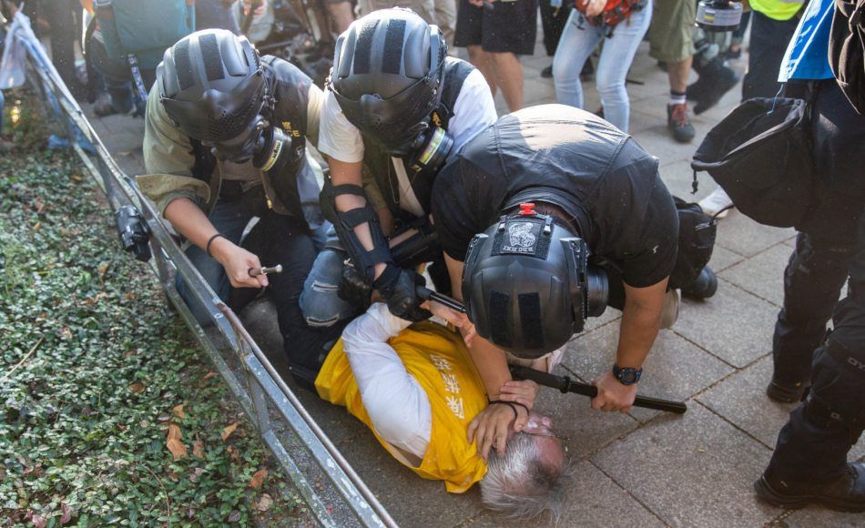 Three Hong Kong police forcing an elderly man onto the ground.