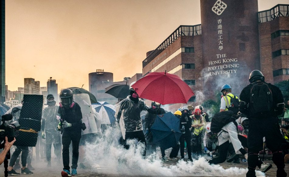 Students in face masks with umbrellas along with medical aid workers stand amidst tear gas canisters lobbed at them by police in front of Hong Kong Polytechnic University on November 17, 2019.