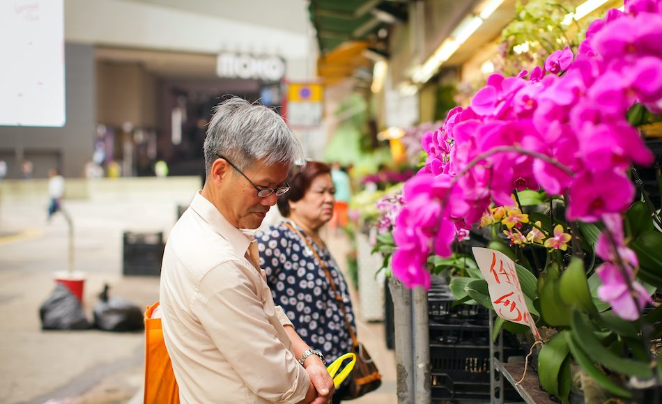 elderly man browses flowers at Hong Kong flower market