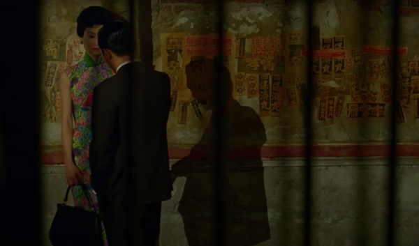 Well dressed man and woman from Hong Kong stand opposite each other on the street at night