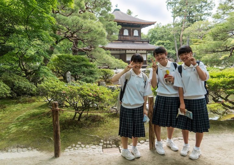3 japanese school girls in uniform smile for a photo out the front of a traditional building and some trees