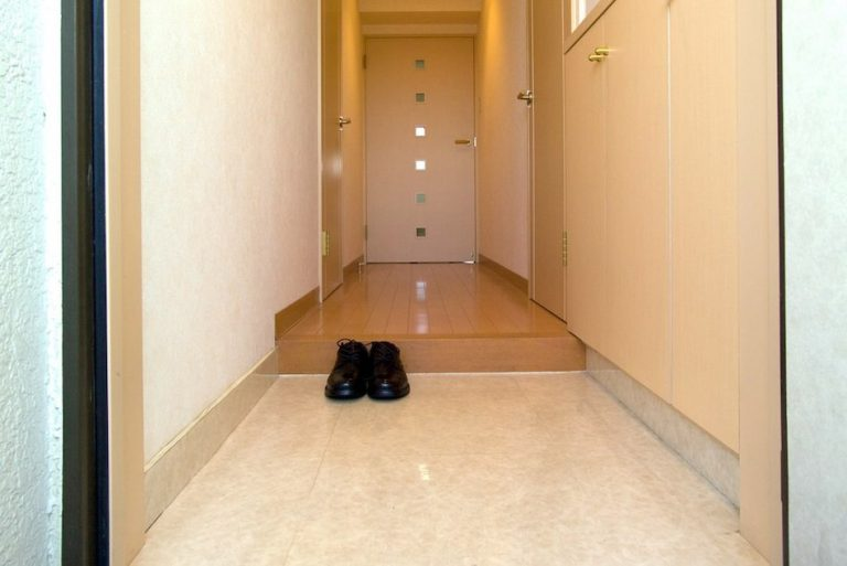 genkan (small entrance in Japan where shoes are kept) one pair of black shoes with toe pointing the direction of the front door