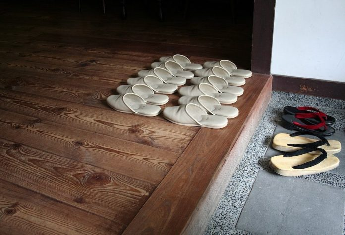 Many pairs of Japanese house slippers lined up and some traditional japanese shoes for outside lay in front.