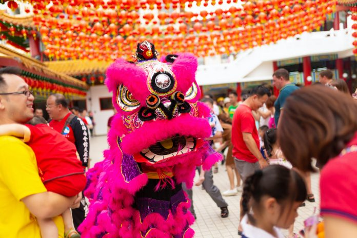 Pink Chinese Dragon in busy street represents legend Nian