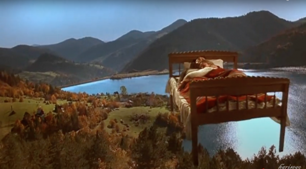couple are in bed as it flies through the sky lake and mountain backdrop below