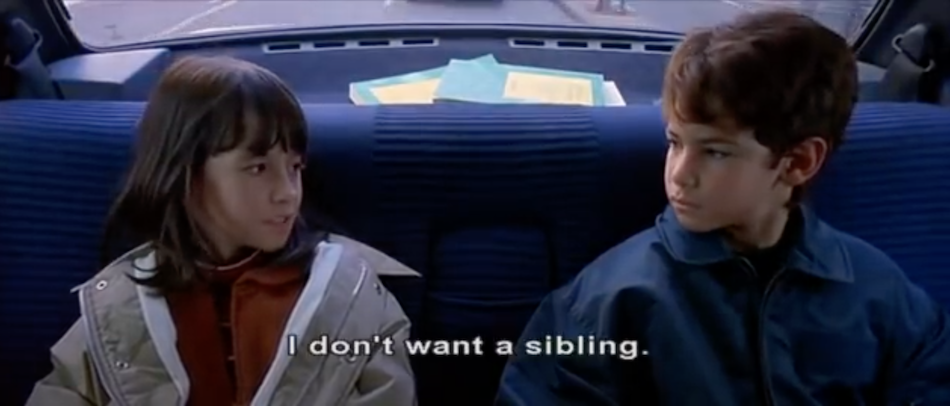 two kids in the back of the car look at each other subtitles say 'I don't want a sibling'